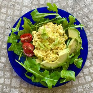 Vegan eggless salad on a plate with greens