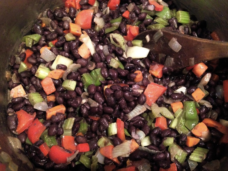 Cuban black bean in a bowl with serving spoon.